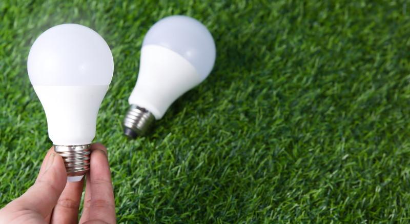 Χέρι κρατάει μια λάμπα LED σε πράσινο ψεύτικο γρασίδι ως background